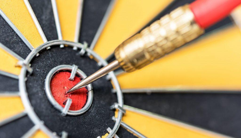Closeup dart target with arrow on bullseye